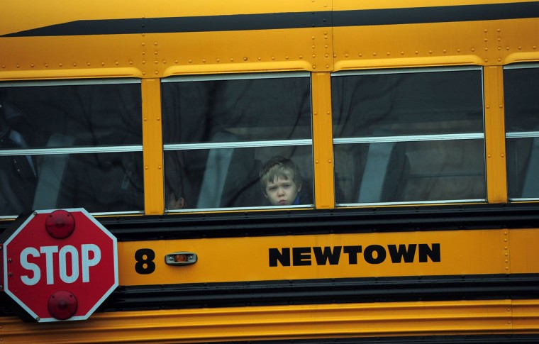A child looks out of a bus window as it passes by Saint Rose of Lima Church where the funeral of James Mattioli, 6 is taking place in Newtown, Connecticut. Lawmakers are under mounting pressure to address the issue of gun laws in the aftermath of last week's school massacre in Newtown, Connecticut. (Emmanuel Dunand/AFP/Getty Images)