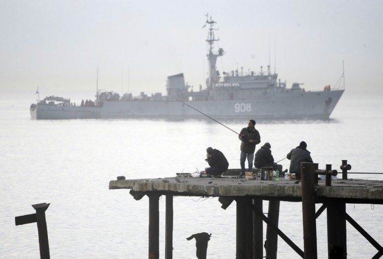 People fishing in front of a Russian border patrol boat in the Black Sea resort of Sochi. Sochi will host the 2014 Winter Olympics that start on February 7, 2014 . (Mikhail Mordasov/Getty Images)