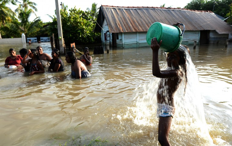 A Sri Lankan flood affected victim washes in a flooded village in the north Western Province town of Chilaw. Flash floods have killed at least 25 people in Sri Lanka and left more than a quarter of a million marooned in their homes, disaster officials said. (Ishara S. Kokikar/ Getty Images)