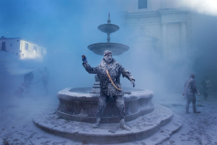 """A military dressed man throws an egg as he takes part in the battle of """"Enfarinats"""", a floor fight in the town of Ibi, in the south-eastern Spain on December 28, 2012. For 200 years Ibi's citizens annually celebrate with a battle using flour, eggs and firecrackers outside the city townhall. (Jaime Reina/Getty Images)"""