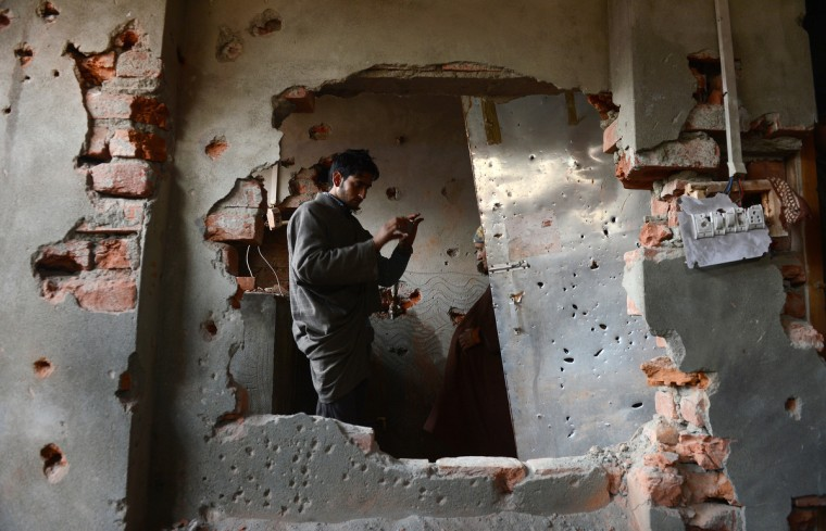 A Kashmiri Muslim looks at a damaged house where Indian troops killed two militants belonging to the Pakistan-based Lashkar-e-Taiba rebel group in Pulwama some 55kms south of Srinagar. Indian troops shot dead two suspected Islamic militants in Kashmir while seven civilians received police bullet injuries when they protested the slaying of the rebels, officials said. The two militants belonging to the Pakistan-based Lashkar-e-Taiba rebel group were killed while three troopers were wounded in a firefight with militants in Pulwama town. (Tauseef Mustafa/Getty Images)
