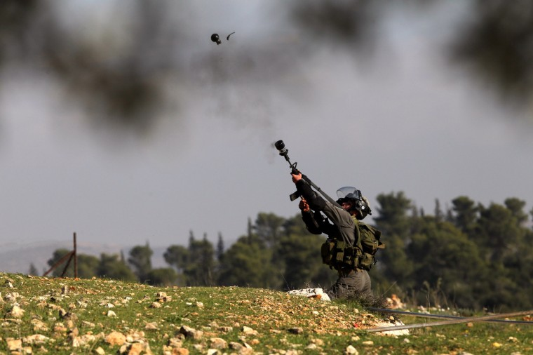 An Israeli border policeman fires a tear gas grenade towards Palestinian protesters during clashes that erupted following a march organized by residents of the West Bank village Nabi Saleh to protest against the expansion of Jewish settlements on Palestinian land. (Abbas Momani/Getty Images)