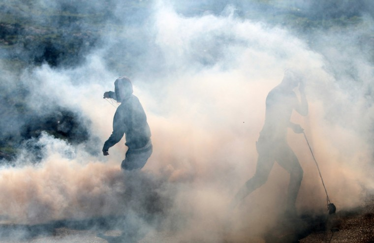 Palestinian protesters stand amid a fog of tear gas fired by Israeli security forces during clashes that erupted following a march organized by residents of the West Bank village Nabi Saleh to protest against the expansion of Jewish settlements on Palestinian land. (Abbas Momani/Getty Images)