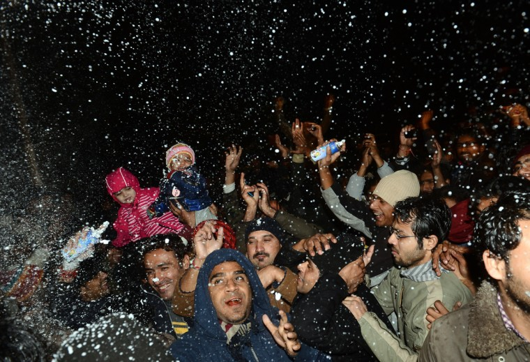 Pakistani youths celebrate the New Year on a street in Lahore on early January 1, 2013. Asian cities brought in the New Year in spectacular style after Sydney set off a global wave of fireworks, with long-isolated Yangon joining the pyrotechnic celebrations for the first time. (Arif Ali/Getty Images)