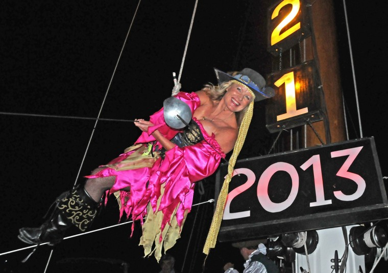 "Evalena Worthington, costumed as a pirate wench, rehearses being lowered from the mast of a sailing vessel at Schooner Wharf Bar on New Year's Eve in Key West, Florida. At midnight, Worthington is to descend as one of five unique ""drops"" in the Florida Keys to herald the dawn of 2013. (Melissa Pearson/Getty Images)"