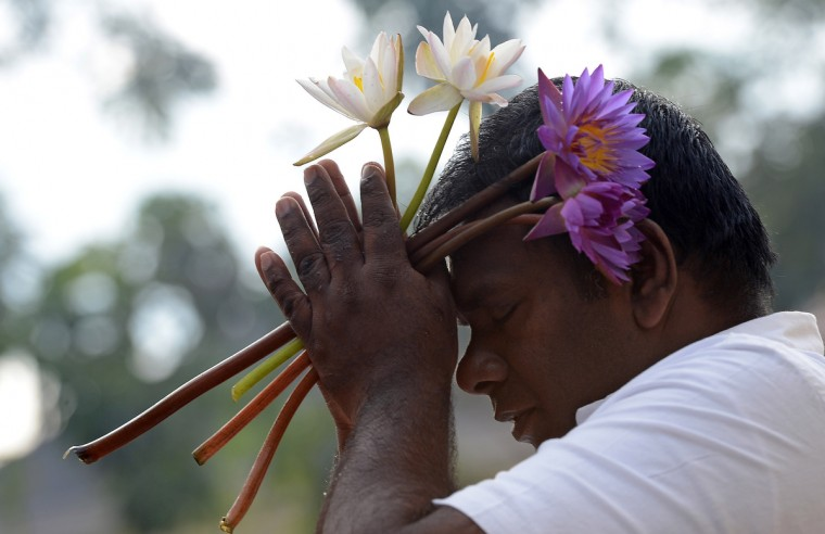 A worshippers prays at a temple in Colombo on January 1, 2013 to welcome in the New Year. Asian cities brought in the New Year in spectacular style the night before after Sydney set off a global wave of fireworks, with long-isolated Yangon joining the pyrotechnic celebrations for the first time. (Getty Images)