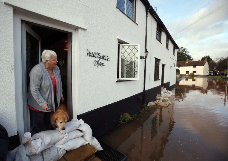 Anne Bartlett and her dog Henry look out from their flooded property in the centre of the village of Ruishton, near Taunton, on November 25, 2012 in Somerset, England. Another band of heavy rain and wind continued to bring disruption to many parts of the country today particularly in the south west which was already suffering from flooding earlier in the week. (Matt Cardy/Getty Images)