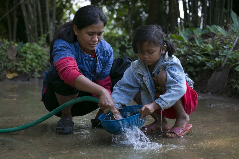 Niang, a mahout's wife and her daughter Ari, 6, wash the coffee beans after picking them from the dung at an elephant camp at the Anantara Golden Triangle resort on December 10, 2012 in Golden Triangle, northern Thailand. (Paula Bronstein/Getty Images)