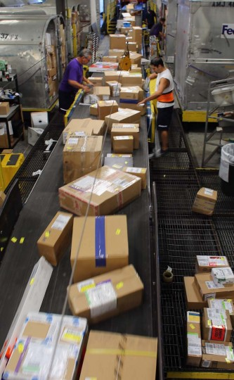 FedEx employees, Rene Carballo (L) and Alexis Barzags, sort through items being shipped through the Fedex World Service Center on December 10, 2012 in Doral, Florida. FedEx Corp. expects today to be the busiest shippping day of the year when 19 million packages are expected to move through their system. (Joe Raedle/Getty Images)