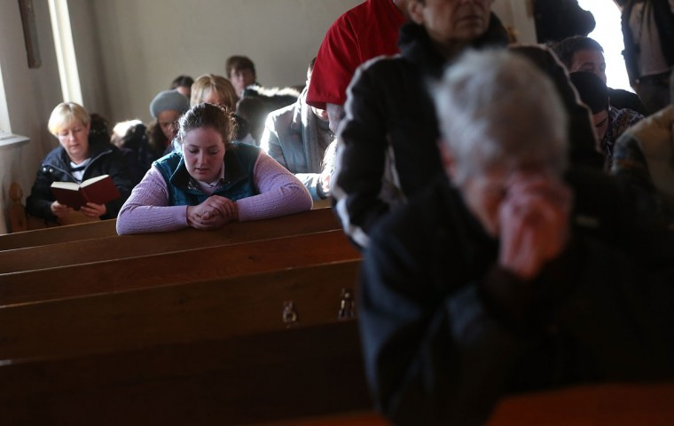 People worship at a prayer service held to reflect on the violence at Sandy Hook Elementary School in Newtown, Connecticut. At least 26 people were shot dead, including 20 children, after a gunman opened fire in the school. (Mario Tama/Getty Images)