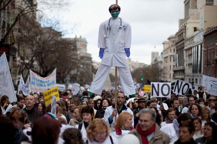 A man holds a dummy depicting a health worker amid other health workers during a demonstration against cuts on public health care and the privatization of medical centers and hospitals on December 16, 2012 in Madrid, Spain. (Pablo Blazquez Dominguez/Getty Images)