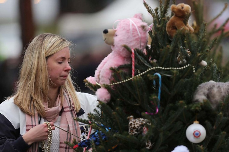 Kat Donohue of Newtown helps to decorate donated Christmas trees placed in front of the Sandy Hook School December 16, 2012 in Newtown, Connecticut. Twenty-six people were shot dead, including twenty children, after a gunman identified as Adam Lanza opened fire at Sandy Hook Elementary School. (Spencer Platt/Getty Images)