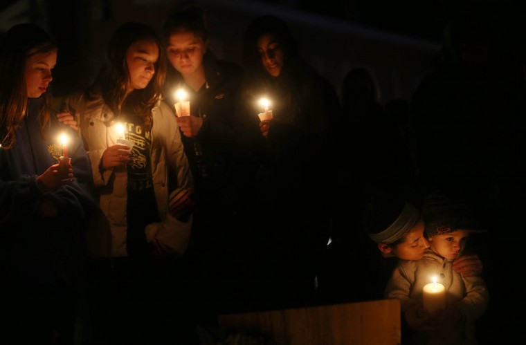 Newtown residents, left to right, Claire Swanson, Kate Suba, Jaden Albrecht, Simran Chand and New London, Connecticut residents Rachel Pullen and her son Landon DeCecco, hold candles at a memorial for victims on the first Sunday following the mass shooting at Sandy Hook Elementary School on December 16, 2012 in Newtown, Connecticut. U.S. President Barack Obama visited the grief stricken town today. (Mario Tama/Getty Images)