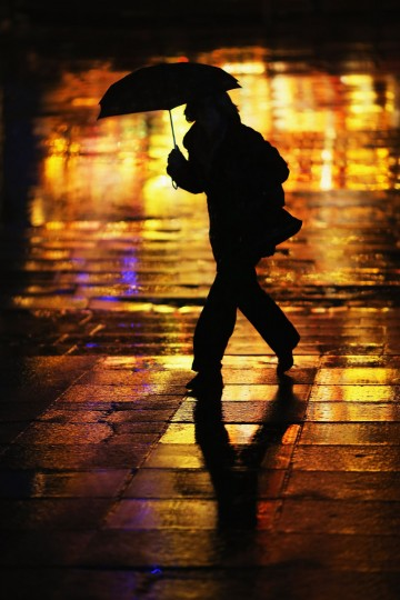 A woman is silhouetted against Christmas lights as she walks down the South Bank area in the rain on December 19, 2012 in London, England. (Dan Kitwood/Getty Images)