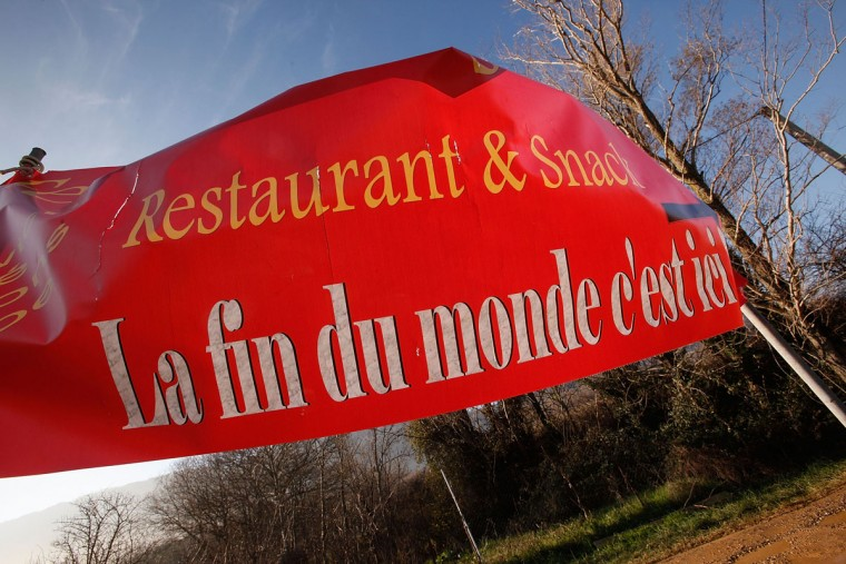 "A sign reading ""The end of the world is here"" advertises a restaurant in Bugarach, the small French village in the foothills of the Pyrenees that some claim to be one of the few places on Earth that will be spared when the world ends on December 21, 2012. Miviludes, the French government's dedicated sect watchdog, are investigating the likelihood of apocalyptic sect activity or ritualized suicides due to the rumored prophecy of the ancient Mayan calendar. (Patrick Aventurier/Getty Images)"