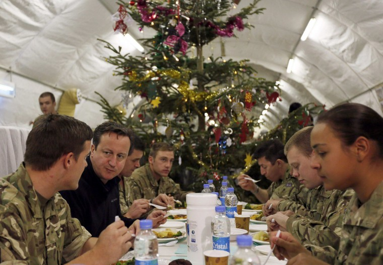 British Prime Minister David Cameron (second from left) eats dinner with British soldiers during a visit to Forward Operating Base Price on December 20, 2012 in Helmand Province, Afghanistan. Cameron made a Christmas visit to British troops in the region amid tight security. (Stefan Wermuth - WPA Pool/Getty Images)