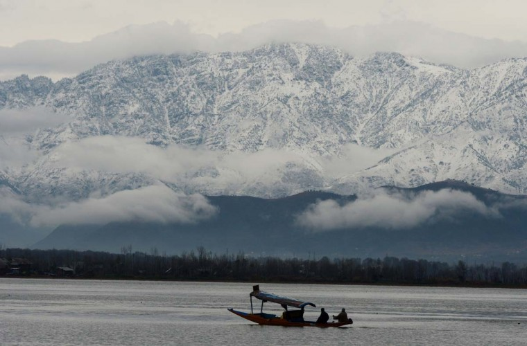 A boat passes in front of snow-covered mountains on Dal Lake in Srinagar on November 29, 2012. The 434-km Srinagar-Leh National highway was closed for traffic as high altitude areas of Kashmir Valley, including the famous ski resort of Gulmarg, experienced the first heavy snowfall of the season, officials said. (Tauseef Mustafa/AFP/Getty Images)