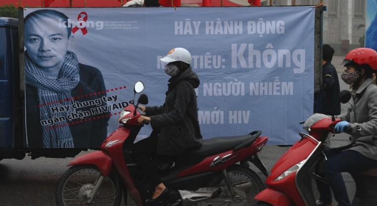 Commuters in Hanoi ride near a truck carrying a poster advertising World AIDS Day on Dec. 1, 2012. Since the first HIV case detected in 1990, the number of cases in Vietnam in 2012 is projected to be 280,000, or 0.47 percent of the Vietnamese population. (Hoang Dinh Nam/AFP/Getty Images)