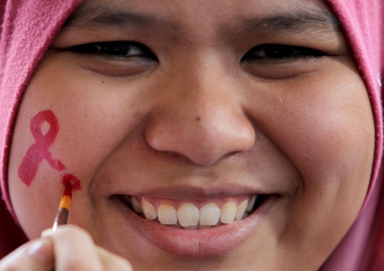 A Malaysian Muslim woman has her face painted during a World AIDS Day campaign in Kuala Lumpur, Malaysia, on December 1, 2012. (Mohd Rasfan/AFP/Getty Images)