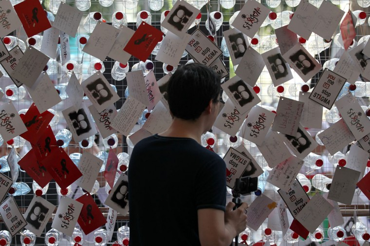 A visitor reads postcards showing support for HIV-positive patients during a World AIDS Day campaign in Kuala Lumpur, Malaysia. (Mohd Rasfan/AFP/Getty Images)