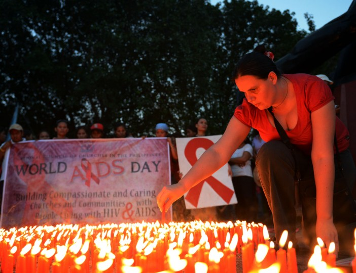 An AIDS activist lights a group of candles placed in the shape of a red AIDS awareness ribbon during an event marking World AIDS Day in Manila, the capital fo the Philippines. Discrimination against homosexuals and people infected with HIV is contributing to the rapid rise of the incurable disease in the nation, officials and health activists said. (Ted Aljibe/AFP/Getty Images)