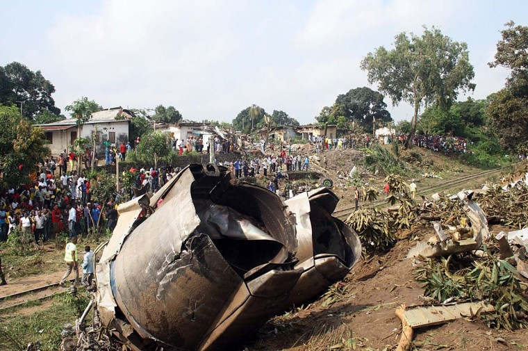 People gather on December 1, 2012 at the site of a Ilyushin cargo plane that crashed late on Nov. 30, 2012 at Brazzaville airport. The plane which was trying to land in a storm near the airport killed about 30 people as it skidded off the runway into houses and a bar in the Congolese capital before crashing into a ravine. The crew, three-four people were thought to have died in the ensuing fire, while another 20 people were injured in the crash and taken to nearby hospitals, witnesses said. (Guy Gervais/AFP/Getty Images)