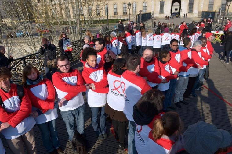 Volunteers hold hands on the Pont des Arts pedestrian bridge in central Paris on December 1, 2012 to create a human chain in the shape of a red AIDS awareness ribbon as part of World AIDS Day. (Miguel Medina/AFP/Getty Images)