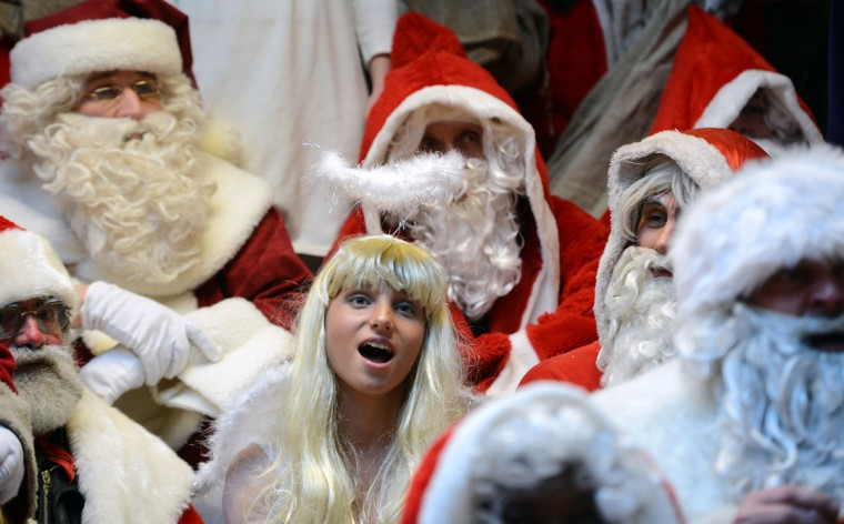 A woman dressed as an angel stands between men dressed as Santa Claus as she attends the annual meeting of volunteer Santa Clauses and Angels on December 1, 2012 in Berlin. The event was organized by Studentenwerk Berlin, a student organization at the German capital's technical university (Technische Universitaet Berlin), that sends out its students dressed as Santas and angels every year to visit company parties in December and families on Christmas Eve. (Johannes Eisele/AFP/Getty Images)