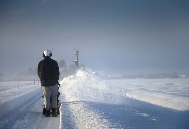 A man uses a snow blower to clear a small road leading to his farm in Saleby, outside Skara in southwestern Sweden on December 1, 2012. (Bjorn Larsson Rosvall/AFP/Getty Images)