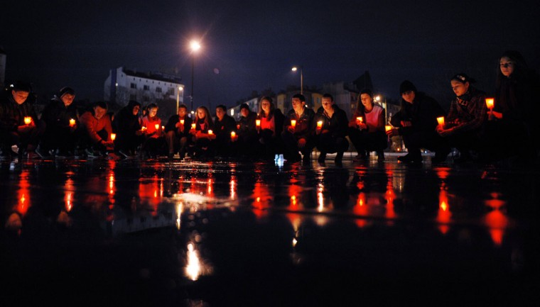 Youths hold candles as they kneel during a flash mob commemorating World AIDS Day in the center of Sofia, the capital of Bulgaria. (Nikolay Doychinov/AFP/Getty Images)