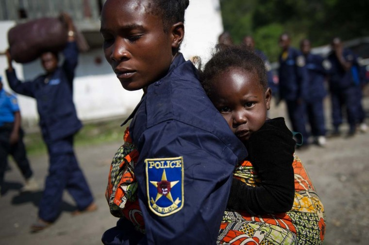 A Congolese national police officer carries her child after disembarking from a boat at the port in the city of Goma, in the east of the Democratic Republic of Congo, on December 2, 2012. After M23 rebels pulled out of Goma yesterday, 166 government police officers arrived this morning from Bukavu. (Phil Moore/AFP/Getty Images)