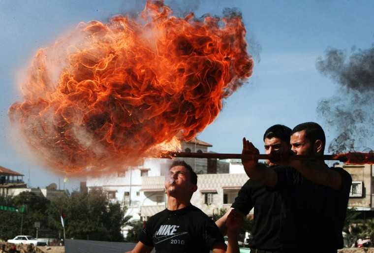 A Hamas security officer blow fire during a graduation ceremony in the destroyed Al-Saraya headquarters in Gaza City on December 2, 2012. (Mahmud Hams/AFP/Getty Images)