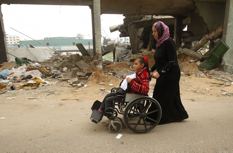 Palestinian children with special needs walk past buildings destroyed during the Gaza-Israeli conflict during a demonstration on the occasion of the UN International Day of People with Disability in Gaza City. (Mohammed Abed/AFP/Getty Images)