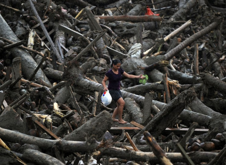 A resident carrying a bag full of relief goods walks amongst typhoon debris as she heads for her home in New Bataan, Compostela Valley province. President Benigno Aquino vowed action on the Philippines' typhoon disasters as bruised and grieving survivors tried to recover from the latest that left nearly 500 people dead. (Ted Aljibe/AFP/Getty Images)