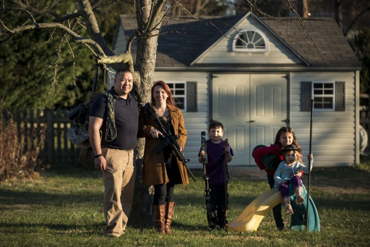 Jay Blevins and his wife Holly Blevins and their children Samuel Benjamin Blevins, 7, Elliana Grace Blevins, 9, and Evangeline Joy Blevins, 4, pose beneath one of their apple trees with survival gear including a buyout bag, an AR-15 rifle and a hunting bow December 5, 2012 in Berryville, Virginia. Jay Blevins and his wife Holly Blevins have been preparing with a group of others for a possible doomsday scenario where the group will have to be self-sufficient due to catastrophe or civil unrest. (Brendan Smialowski/AFP/Getty Images)