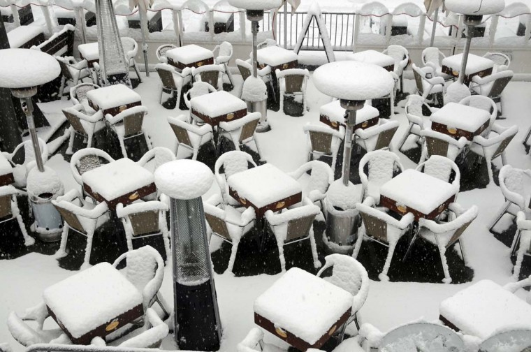 Tables and chairs are covered in snow outside a restaurant at the Rhine Promenade in Duesseldorf, western Germany, on December 7, 2012. (Horst Ossinger/AFP/Getty Images)