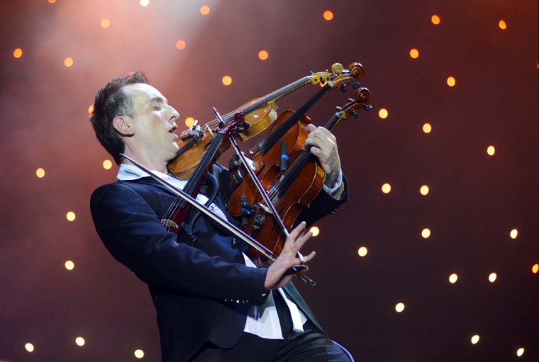"""Ukrainian virtuoso violinist Oleksandr Bozhyk plays four violins at the same time as he performs ''Requiem for a Dream"""" by Clint Mansell during his solo concert in the western Ukrainian city of Lviv on December 8, 2012. (Yuriy Dyachyshyn/AFP/Getty Images)"""