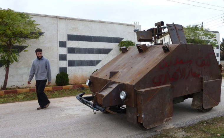 """From a distance it looks rather like a big rusty metal box but closer inspection reveals the latest achievement of Syrian rebels: a homemade armored vehicle waiting to be deployed. Sham II, named after ancient Syria, is built from the chassis of a car and touted by rebels' Al-Ansar brigade as """"100 percent made in Syria."""" Here it is seen in Bishqatin, 4 kms west of Aleppo, on December 8, 2012. (Herve Bar/AFP/Getty Images)"""