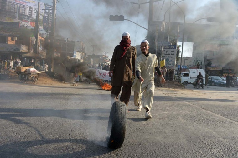 Pakistani Islamists roll a tire as they block a street during a protest in Islamabad on December 9, 2012, against Iftikhar Ahmed, the author of an alleged anti-Islamic book. Some four hundred religious students held a protest to pressure police to register a case in a blasphemy row against Ahmed. (Farooq Naeem/AFP/Getty Images)