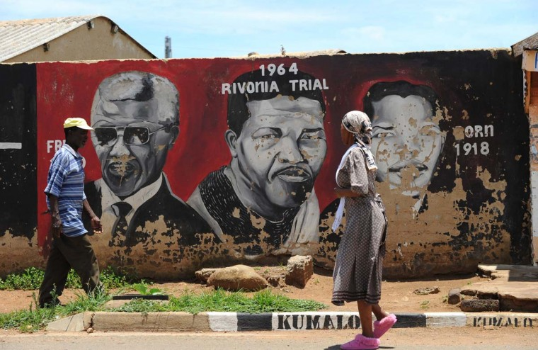 Soweto's residents walk past portraits of former South Africa's president Nelson Mandela painted on a wall, on December 10, 2012 in Soweto. Mandela is set to undergo more undefined medical tests on December 10, 2012, the South African government announced. (Alexander Joe/AFP/Getty Images)