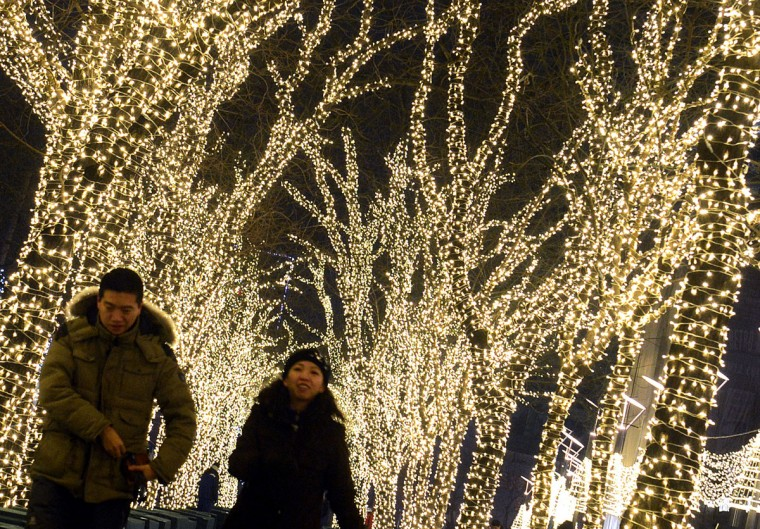 A Chinese couple walk past trees decorated for the winter holidays in Beijing. Mathematics has provided an answer for those striving for the perfect Christmas tree, Britain's University of Sheffield said. Their formula states that a 180-centimeter (roughly six feet) Christmas tree would need 37 baubles, around 919 centimeters of tinsel (30 feet), 565 centimeters (19 feet) of lights, and an 18-centimeter (seven-inch) star or angel to achieve the perfect look. (Mark Ralston/AFP/Getty Images)