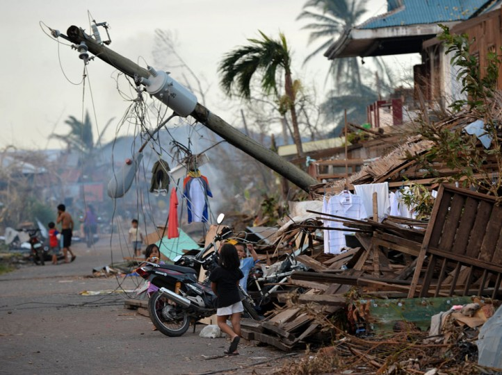 Children walk near a toppled electric post in Boston town, Davao Oriental province on December 10, 2012. (Ted Aljibe/AFP/Getty Images)