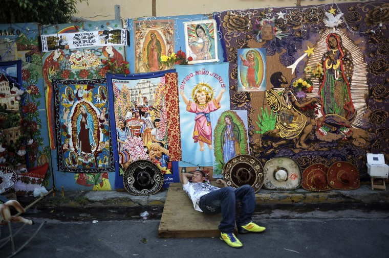 A street vendor lays next to religious merchandise portraying the Virgin of Guadalupe near the Basilica de Guadalupe in San Salvador. Salvadorean faithfuls celebrated the appearance of the Virgin of Guadalupe to Juan Diego in 1531. (Jose Cabezas/Getty Images)