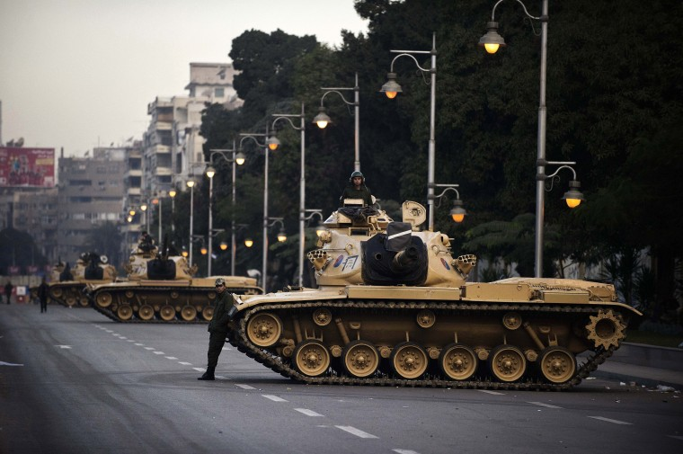 Egyptian army tanks are deployed outside the presidential palace in Cairo. Egypt's crisis showed no sign of easing as the army delayed unity talks meant to ease political divisions and the opposition set near-impossible demands for taking part in a looming constitutional referendum. (Gianluigi Guercia/Getty Images)