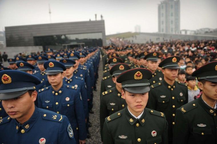 Chinese military personnel attend a a ceremony for victims on the 75th anniversary of the Nanjing massacre at the Memorial Museum in Nanjing. Air raid sirens sounded in the Chinese city of Nanjing as it marked the 75th anniversary of the mass killing and rape committed there by Japanese soldiers -- with the Asian powers' ties at a deep low. (Peter Parks/Getty Images)