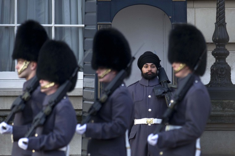 Sikh Scots Guards soldier Jatenderpal Singh Bhullar (2-R), stands on guard duty outside Buckingham Palace in central London on. Jatenderpal Singh Bhullar became the first guardsman to parade outside Buckingham Palace wearing a turban instead of the bearskin. (Carl Court/Getty Images)
