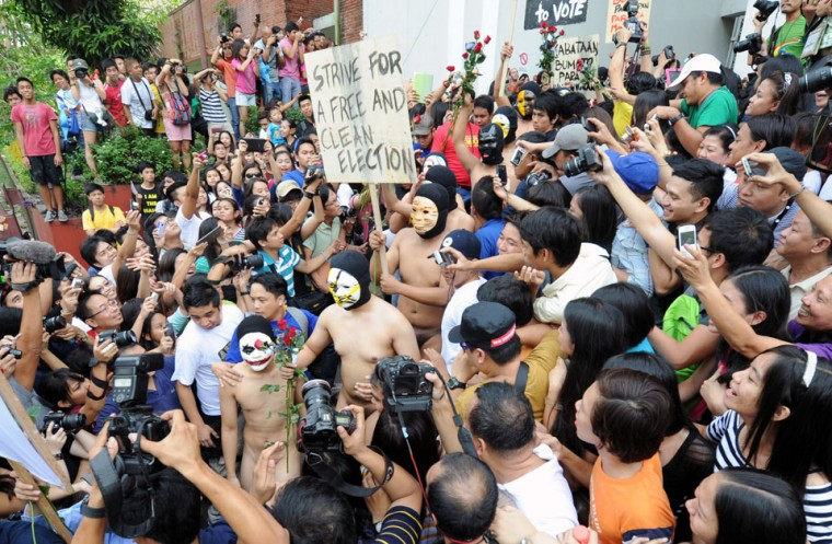 A group of masked fraternity members (C) in the state-run University of the Philippines runs naked through campus during the annual Oblation Run, handing out roses to female students as part of their tradition in Manila. This year's run was dedicated to the holding of free and clean elections next year in a country known for violence and voter fraud during polls. (Jay Directo/AFP/Getty Images)