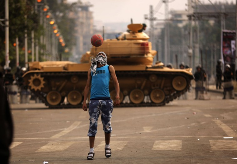 A supporter of the opposition to Egyptian President Mohamed Morsi plays football next to a Republican Guard tank deployed outside the presidential palace in Cairo. Egypt's 51 million voters are being called to vote over the next two weekends in a referendum on a draft constitution backed by Islamists, including Morsi, but denounced by the secular opposition. (Patrick Baz/AFP/Getty Images)