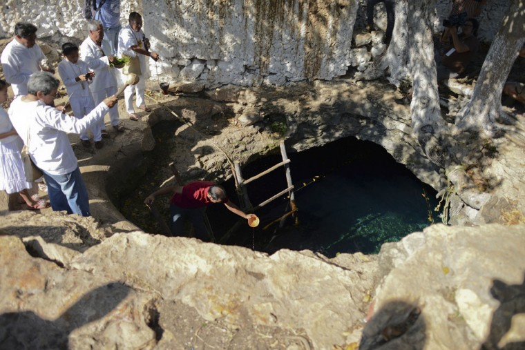 Maya priests hold a water blessing ceremony at the Noc Ac cenote (a natural deep deposit of water) in the town of the same name in Mexico, on December 15, 2012. The ceremony was part of a Mayan culture festival held, according to organizers, to honor Mayan culture and to promote intercultural dialogue. An additional goal was to help the public better understand the end of the Mayan Long Count calendar, which many have interpreted to be a Mayan prediction of the apocalypse. (Francisco Martin/Reuters)