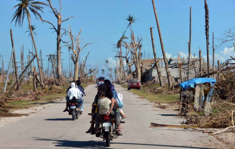 This photo taken on December 11, 2012 shows a family on a motorcycle riding past destroyed coconut trees in Cateel in Davao Oriental province after Typhoon Bopha hit the province on December 4. The death toll from the strongest typhoon to hit the Philippines this year has topped 1,000 and could still rise sharply, the government said on December 16, 2012. (Ted Aljibet/AFP/Getty Images)
